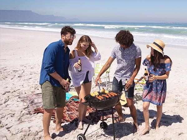 A group of friends enjoying a braai on the beach using Etosha braai products.